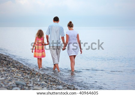 Happy family with little girl walk on beach in evening - stock photo