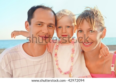 Happy family with little near to sea - stock photo