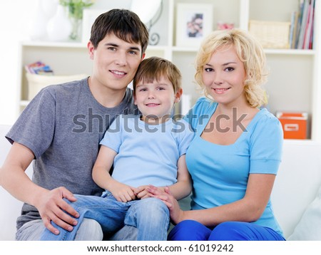 Happy family with little son sitting together on the sofa at home - indoors - stock photo