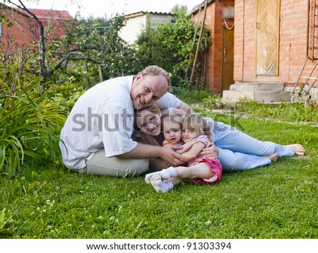 Happy family with 6 month and 2 years old baby daughters on a lawn