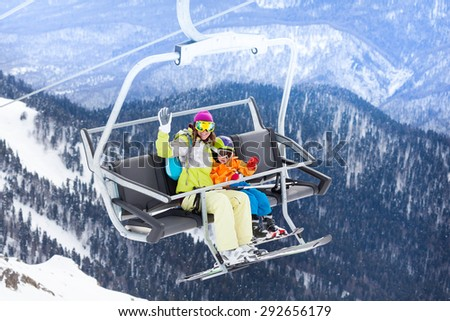 Happy family with mother and little boy sitting on ski lift waving hand with mountains and forest on background