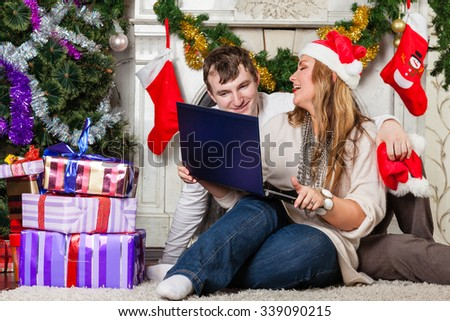 Happy family with notebook sitting near Christmas tree at home. - stock photo