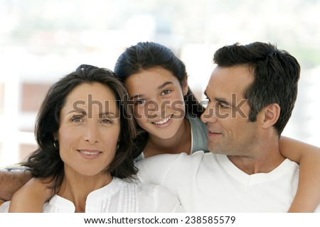 Happy family with one child. Daughter between her parents sitting on sofa. Close-up. - stock photo