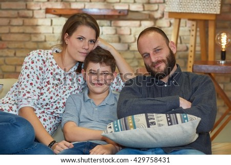 Happy family with one child sitting at home, smiling.