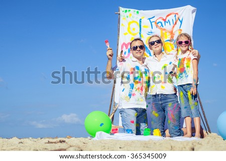 Happy family with paint  playing on the beach at the day time. Concept of friendly family. - stock photo