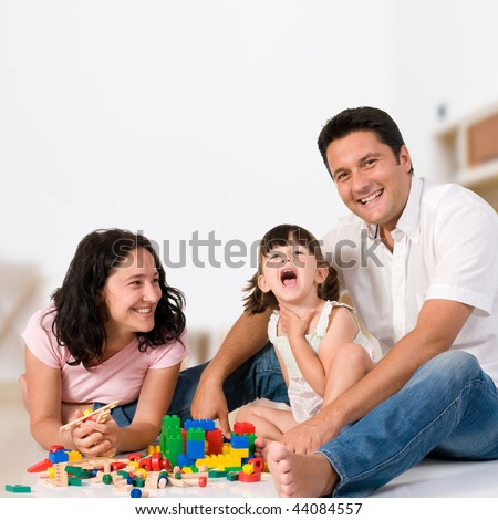 Happy family with parents and daughter playing with colorful blocks inside at home - stock photo