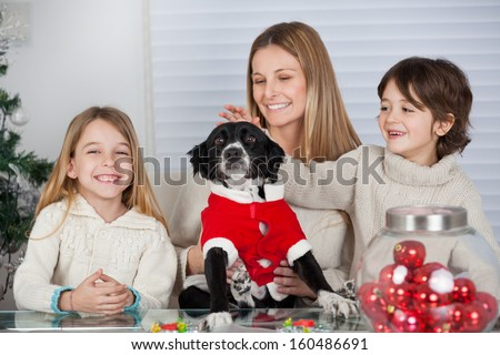 Happy family with pet dog sitting at home during Christmas - stock photo