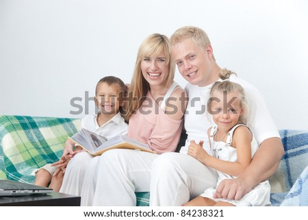 Happy family with photo album on sofa