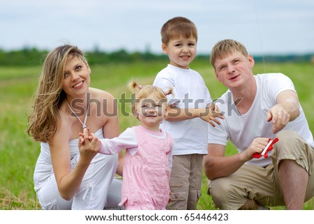 Happy family with pregnant wife fly a kite together in summer field - stock photo