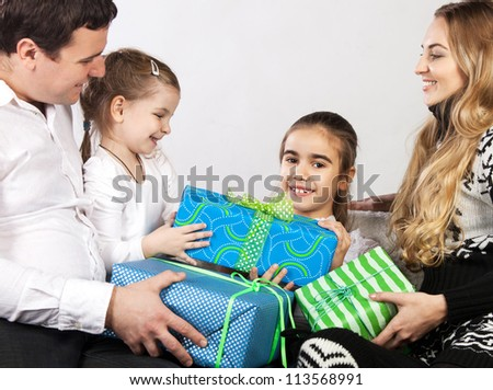 Happy family with presents. Father and mother give presents to they daughter - stock photo