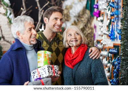 Happy family with presents shopping in Christmas store - stock photo