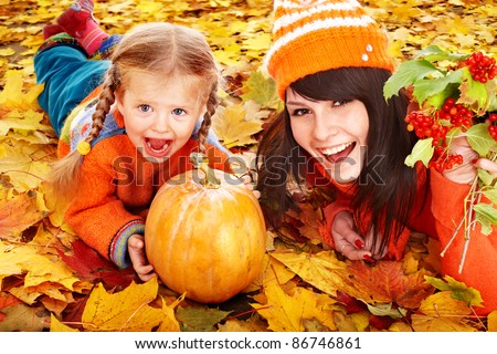 Happy family with  pumpkin on autumn leaves. Outdoor. - stock photo