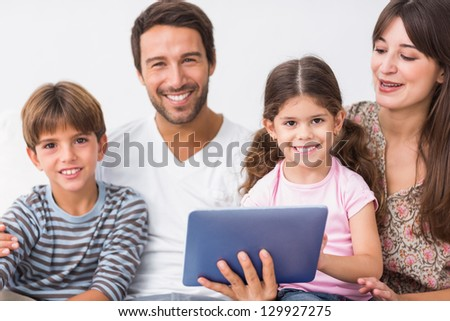 Happy family with tablet pc on the couch - stock photo