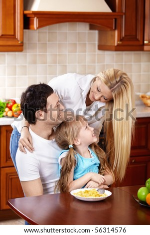 Happy family with the child in kitchen during a breakfast