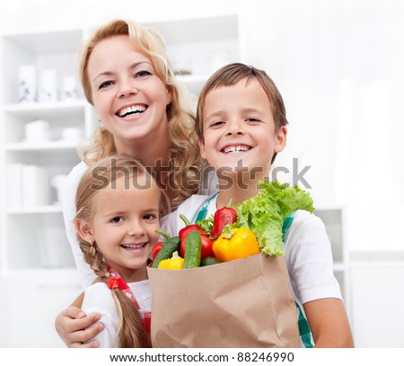 Happy family with the grocery bag full of fresh vegetables - healthy life concept - stock photo
