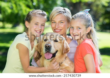 Happy family with their dog on a sunny day - stock photo