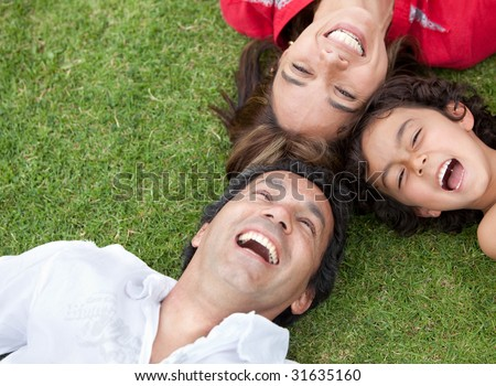 Happy family with their heads together on the floor outdoors - stock photo