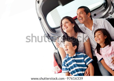 Happy family with their new car smiling - stock photo