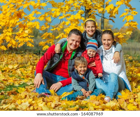 Happy family with three kids at beautiful autumn park - stock photo