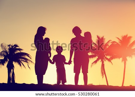 happy family with tree kids at sunset tropical beach