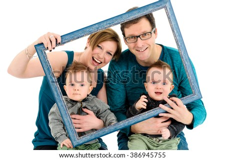Happy family with twins is laughing.  They are holding a picture frame to make a creative effect on family portrait. Isolated on white. - stock photo