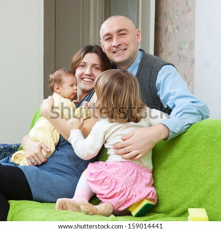Happy family with two children enjoying time in living room at their home - stock photo