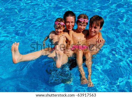 Happy family with two children having fun in swimming pool - stock photo