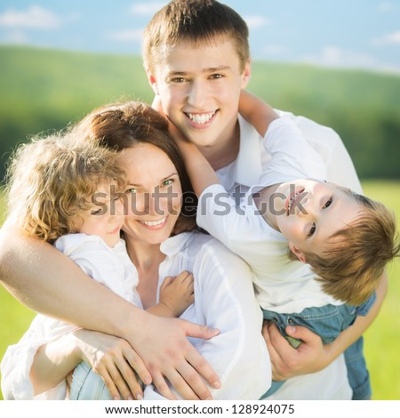 Happy family with two children having fun outdoors in spring field against blue sky background. Farmland vacations concept - stock photo