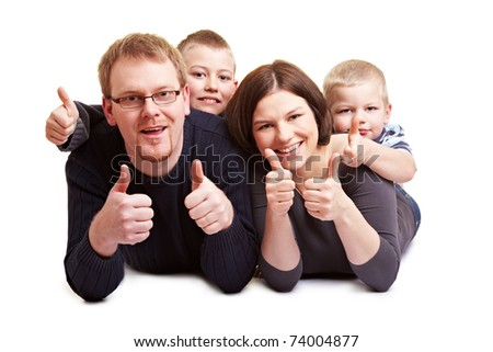 Happy family with two children holding their thumbs up
