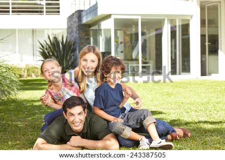 Happy family with two children laying in a garden in front of modern house