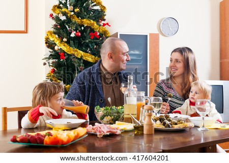 Happy family with two children near Christmas tree  over celebratory table - stock photo