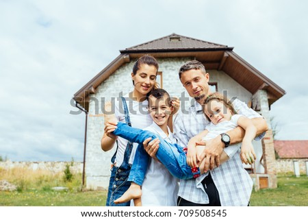 Happy family with two children near new home. Real estate background. New housing, parenthood and children concept.