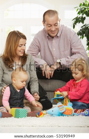 Happy family with two children playing on floor in living room at home sitting on floor in front of sofa.
