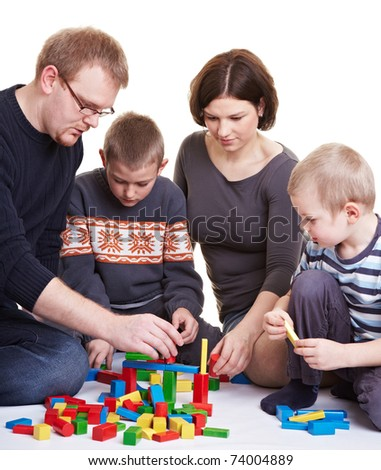 Happy family with two children playing together with building bricks - stock photo