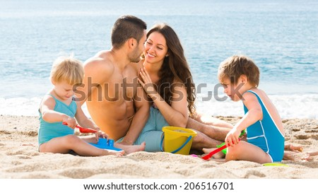 Happy family with two children spending  weekend at the beach - stock photo