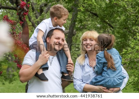 Happy family with two children walking in spring garden