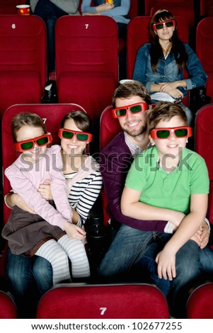Happy family with two children watching a movie - stock photo