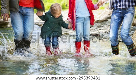 Happy family with two children wearing rain boots jumping into a mountain river. Photo in motion. DOF