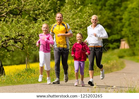 Happy Family with two girls running or jogging for sport and better fitness in a meadow in summer - stock photo
