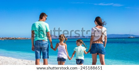 Happy family with two kids during tropical beach vacation - stock photo