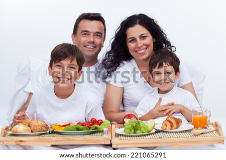 Happy family with two kids having breakfast in bed - healthy eating at home - stock photo
