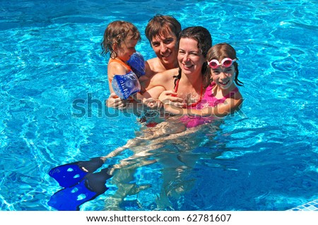 Happy family with two kids having fun in the swimming pool - stock photo
