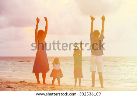 happy family with two kids having fun on sunset tropical beach - stock photo