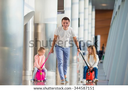 Happy family with two kids in airport have fun waiting for boarding