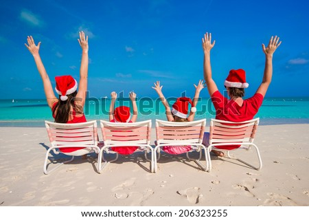 Happy family with two kids in Santa Hat on summer vacation - stock photo
