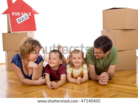 Happy family with two kids in their new home laying on the floor among cardboard boxes - stock photo