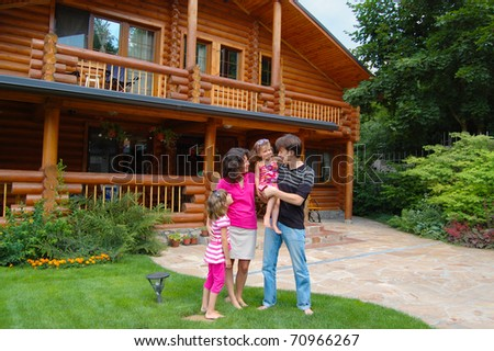 Happy family with two kids near wooden house - stock photo
