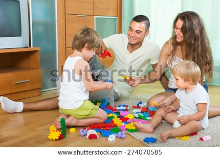 Happy family with two little children playing with plastic toys in home