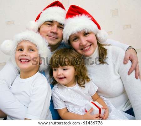 happy family with two small children in Christmas caps rejoices together - stock photo