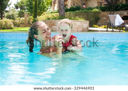 Happy family, young active mother and adorable curly little baby having fun in a swimming pool, child learning to swim in an inflatable toy ring, enjoying summer vacation at a tropical resort